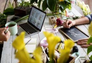 Person working on laptop at a counter in a flower shop with another person writing open on a sign