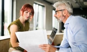 man in business suit explaining concept to woman with red hair