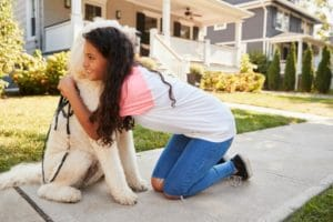 Young girl hugging a dog while kneeling on a sidewalk outside of a suburban home